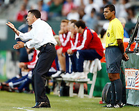 NY Red Bulls head coach, Juan Carlos Osorio relays instructions to his team from the sidelines as 4th official Yader Reyes looks on from behind. Chivas USA  took on the NY Red Bulls on June 28, 2008 at the Home Depot Center in Carson, CA. The game ended in a 1-1 tie.