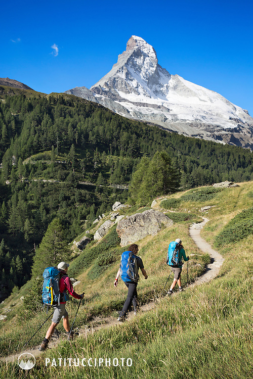 Three hikers on a grassy trail with the Matterhorn above on the sixth, and final day of the Chamonix to Zermatt Glacier Haute Route