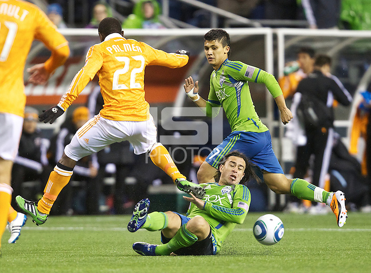 Seattle Sounders FC forward Mauro Rosales slides under Houston Dynamo midfielder Lovel Palmer during play at Qwest Field in Seattle Friday March 25, 2011. In the background is Seattle Sounders FC forward Fredy Montero. The match ended in a 1-1 draw.
