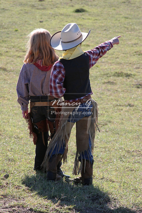 A young cowgirl and cowboy on the range pointing
