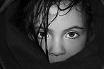 Black and white image of a young female child wrapped in a blanket looking out with large eyes and wet hair..