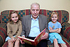 Grandfather reading granddaughters a story,