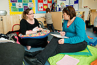 "A mother breastfeeding her baby at a drop-in breastfeeding support centre while talking to the breastfeeding consultant.<br /> <br /> Image from the ""We Do It In Public"" documentary photography project collection: <br />  www.breastfeedinginpublic.co.uk<br /> <br /> Dorset, England, UK<br /> 17/04/2013"