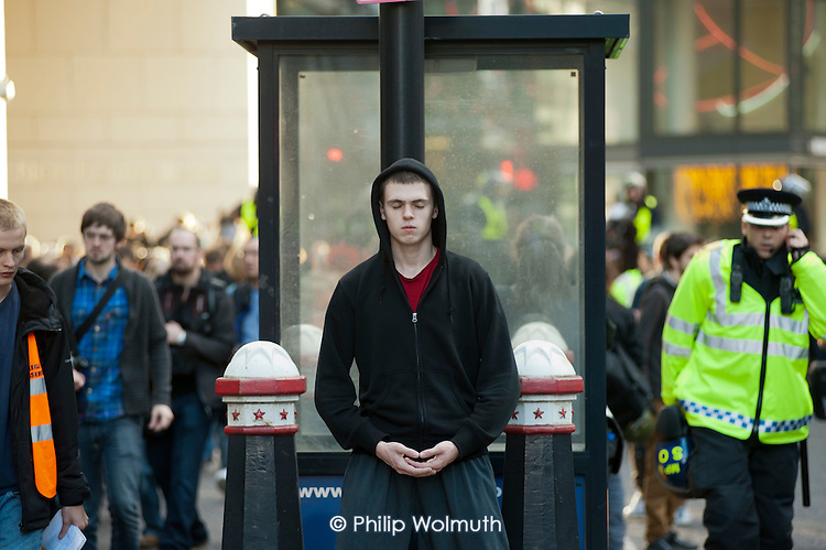 A young man in a hoody meditates during a National Campaign against Fees and Cuts march through the City of London.
