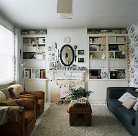 A cosy sitting room in neutral tones. One wall is covered with a floral pattern wallpaper. Cupboards and shelving have been built into the recesses either side of a fireplace. A grey sofa and brown leather armchairs face each other across an antique wooden trunk which acts as a coffee table.