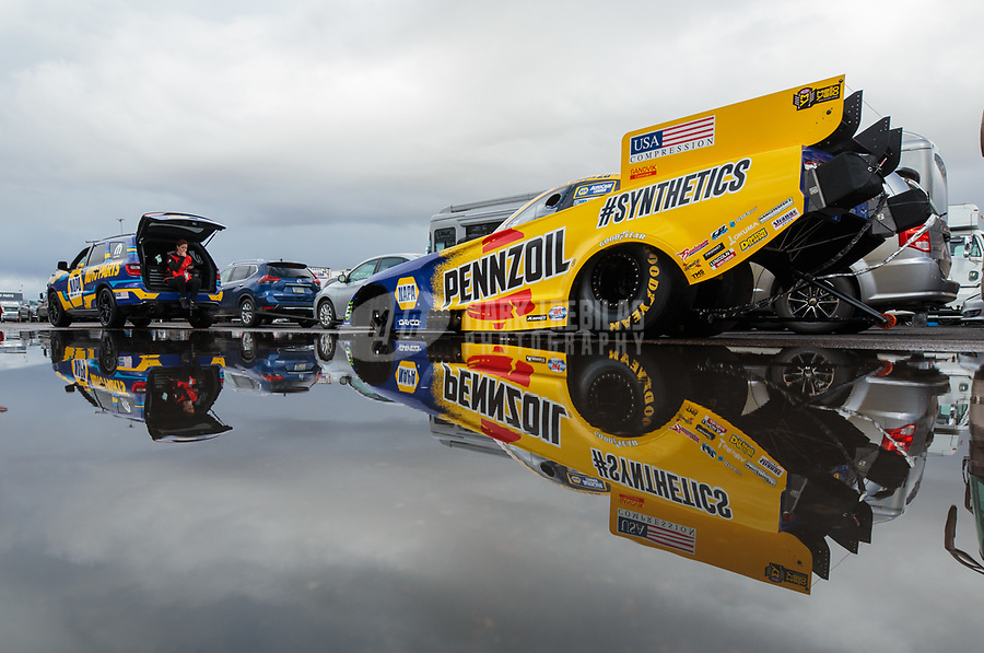 Feb 22, 2019; Chandler, AZ, USA; The car of NHRA funny car driver Ron Capps reflects in a rain puddle as the car is towed to the staging lanes during qualifying for the Arizona Nationals at Wild Horse Pass Motorsports Park. Mandatory Credit: Mark J. Rebilas-USA TODAY Sports