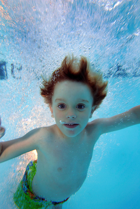 A young boy swims underwater in a pool.
