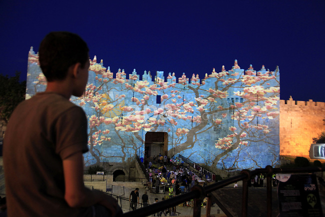 A Palestinian boy looks on Jerusalem's old city Damascus Gate illuminated by light show projected on to its ancient walls during the Jerusalem Festival of Lights on June 4, 2013. Al-Aqsa Foundation for Endowment and Heritage warned of the Israeli Judaization aims behind organizing Festival of Lights in the Old City of occupied Jerusalem at the gates of al-Aqsa Mosque. Photo by Saeed Qaq