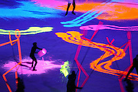 Colorful phosphors illuminated by black light light up the ice at the closing ceremony of the 2002 Winter Games.