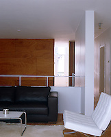 The open-plan living room at the top of the staircase contains several classic pieces of furniture including a Mies van der Rohe Barcelona chair and a Marcel Breuer tubular stainless-steel table