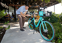 NWA Democrat-Gazette/DAVID GOTTSCHALK Dane Eifling, Bicycle and Pedestrian Program Coordinator with the University of Arkansas and city of Fayetteville, uses Friday, August 3, 2018, the VeoRide app to unlock one of the demonstration bikes for the new bike-share program in the city. The city of Fayetteville, University of Arkansas, Fayetteville and Experience Fayetteville teamed up to bring the program for the bikes that will be red and white with signage.