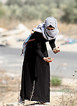 A female Palestinian protester holds stones during clashes with Israeli security forces at the Hawara checkpoint, south of the West Bank city of Nablus, on October 12, 2015. Three new stabbings in Jerusalem and a car attack spread more fear among Israelis as Palestinian unrest showed little sign of slowing after nearly two weeks of violence. Photo by Nedal Eshtayah