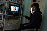 Palestinian Mohamed Hasan, watch news about his cousin US army psychiatrist Major Nidal Malik Hasan, who shot dead 13 people in a US Army base in Texas, at his family house in the West Bank town of Al-Bireh on Nov 7,2009. A stunned nation battled to understand today why the Palestinian immigrant Muslim army psychiatrist snapped, mowing down 12 soldiers and one civilian and wounding 30 others in a trail of bloodshed. Photo by Issam Rimawi