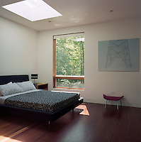 A light-filled bedroom has views of the surrounding woodland through a large window adjacent to the double bed