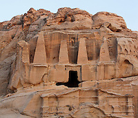 "Obelisk tomb, 1st century AD in Bab as-Siq and Triclinium, 25-75 AD, Petra, Ma'an, Jordan. These 2 Nabatean monuments are carved into the sandstone cliff. The upper Obelisk Tomb is crowned with four elongated pyramids representing ""nefesh"", Nabatean signs commemorating the deceased. The lower gabled facade is the triclinium, a funerary dining hall with benches carved along 3 of its sides, where banquets were held in honour of a god or ancestor. Petra was the capital and royal city of the Nabateans, Arabic desert nomads. Picture by Manuel Cohen"