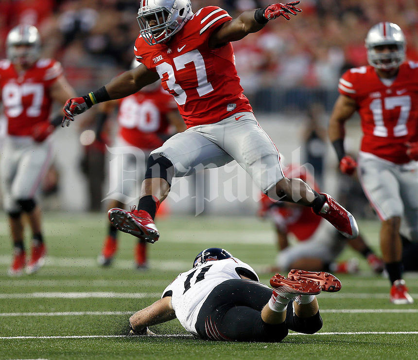 Ohio State Buckeyes linebacker Joshua Perry (37) leaps over Cincinnati Bearcats quarterback Gunner Kiel (11) during the second quarter of Saturday's NCAA Division I football game at Ohio Stadium in Columbus on September 27, 2014. (Columbus Dispatch photo by Jonathan Quilter)