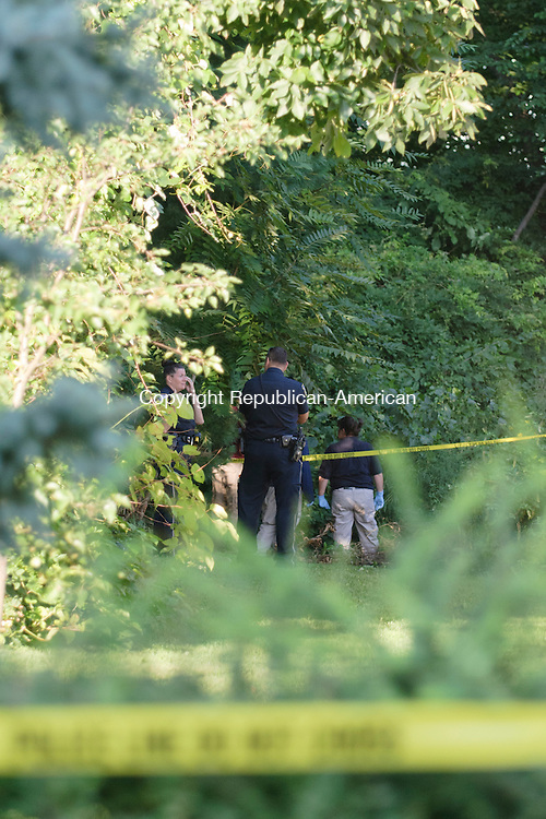 WATERBURY, CT - 16 August 2012-081612EC02--   Waterbury police stand in a wooded area between 135 and 151 Park Terrace in Waterbury Thursday evening surrounded by police tape.  Police have issued a news release confirming a body has been found.  Erin Covey Republican American.
