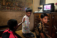 Mohammad Sharif, center, watches a cricket match on television with his friends in Chittagong, Bangladesh.