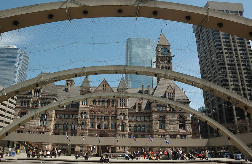 Toronto's Old City Hall seen through the patchwork quilt of bird netting draped over the arches of Nathan Philips Square
