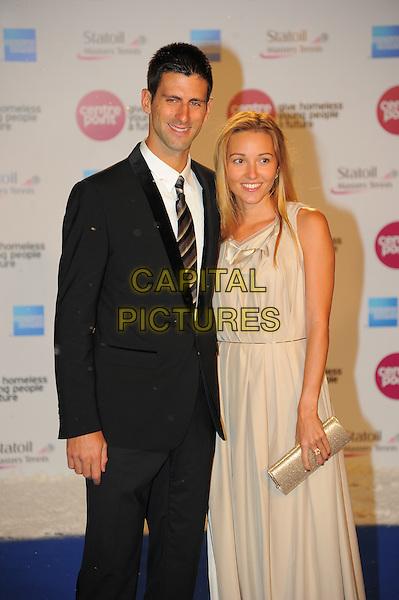 Novak Djokovic & Jelena Ristic.Winter Whites Gala Tennis, Royal Albert Hall, London, England..December 8th, 2012.half 3/4 length black suit white shirt couple beige cream dress  .CAP/CAS.©Bob Cass/Capital Pictures.