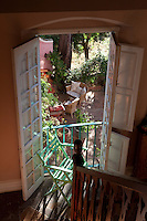 View from the staircase through the open French windows to the courtyard below