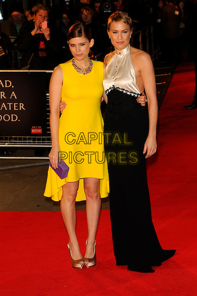 Kate Mara & Robin Wright .'House of Cards' Netflix Gala Screening at the Odeon West End, Leicester Square, London, UK,.January 17th 2012..full length yellow dress sleeveless clutch bag purple black white high neck halterneck buttons lace long maxi silk satin .CAP/CJ.©Chris Joseph/Capital Pictures.