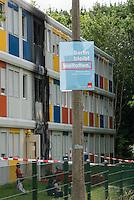 """Brandanschlag auf Fluechtlingsunterkunft in Berlin-Buch.<br /> Am Montag den 8. August 2016 veruebten Unbekannte gegen 3.00 Uhr einen Brandanschlag auf eine Fluechtlingsunterkunft in Berlin-Buch. Sie warfen einen Molotowcoctail durch ein Fenster in das Haus und setzten das Gebaeude in Brand. Die Flammen schlugen bis in den zweiten Stock des Wohncontainers. Die Bewohner retteten schlafende Bewohner aus den oberen Stockwerken und <br /> loeschten den Brand selber mit Feuerloeschern bevor Feuerwehr und die Polizei kamen. Nach Angaben von Bewohnern muessen jetzt wahrscheinlich 180 Menschen aus den Wohncontainern ausziehen, da die Elektrik durch den Brand schwer beschaedigt wurde.<br /> Im Bild: Ein Wahlplakat der SPD mit dem Slogan """"Berlin bleibt weltoffen"""" haengt vor der Fluechtlingsunterkunft.<br /> 8.8.2016, Berlin<br /> Copyright: Christian-Ditsch.de<br /> [Inhaltsveraendernde Manipulation des Fotos nur nach ausdruecklicher Genehmigung des Fotografen. Vereinbarungen ueber Abtretung von Persoenlichkeitsrechten/Model Release der abgebildeten Person/Personen liegen nicht vor. NO MODEL RELEASE! Nur fuer Redaktionelle Zwecke. Don't publish without copyright Christian-Ditsch.de, Veroeffentlichung nur mit Fotografennennung, sowie gegen Honorar, MwSt. und Beleg. Konto: I N G - D i B a, IBAN DE58500105175400192269, BIC INGDDEFFXXX, Kontakt: post@christian-ditsch.de<br /> Bei der Bearbeitung der Dateiinformationen darf die Urheberkennzeichnung in den EXIF- und  IPTC-Daten nicht entfernt werden, diese sind in digitalen Medien nach §95c UrhG rechtlich geschuetzt. Der Urhebervermerk wird gemaess §13 UrhG verlangt.]"""