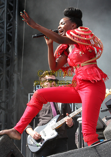 Shingai Shoniwa.THE NOISETTES perform at Day Two V Festival at Hylands Park, Chelmsford, Essex, England..August 21st, 2011.stage concert live gig performance music full length red pink trousers top jacket epaulettes shoulder pads gold fringed tassels singing hair up bun hand arm leg up.CAP/ROS.©Steve Ross/Capital Pictures