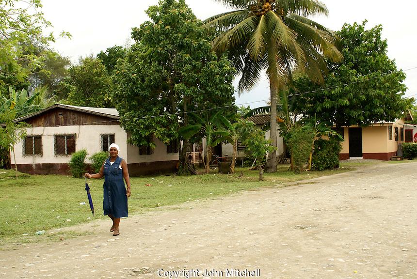 Garifuna woman walking along a street in the Garifuna village of Triunfo de la Cruz, Honduras...