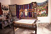 Ollantaytambo, Peru. Small loom and woven items made by the weaver hanging on the walls.