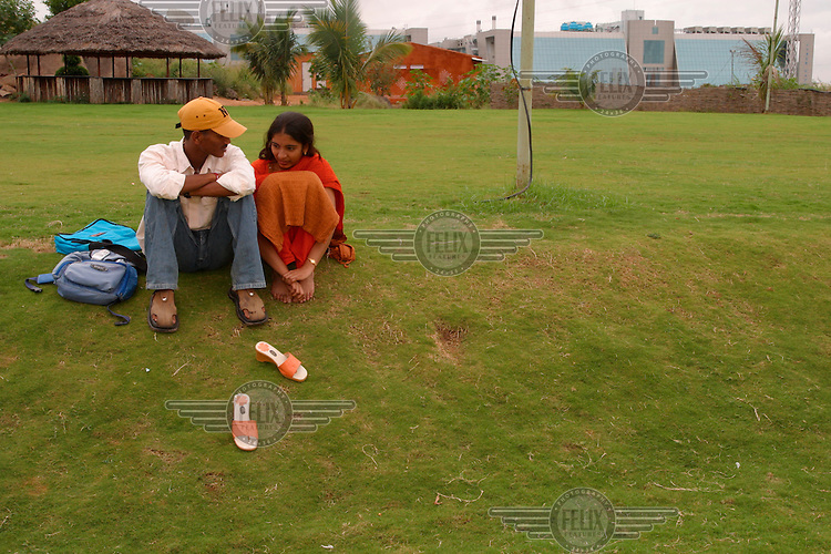 A young couple sit in a park in Hi-tech City.
