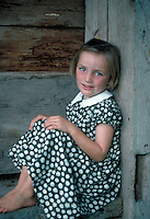 Smiling young girl wearing black flowered dress in rustic setting. Leoni. Germany.
