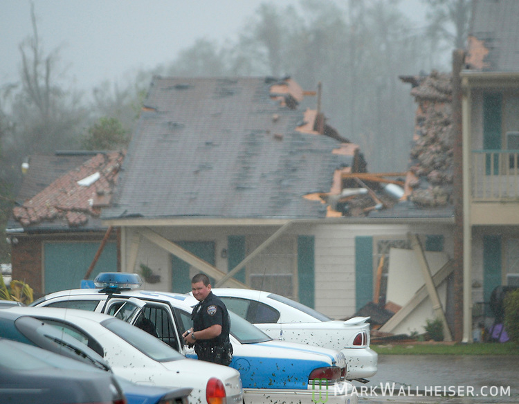 Gulfport Mississippi police officer Jason Payne gets into his patrol car as Hurricane Katrina continues to rage at the Thomasville Apartments in Biloxi after he and others rescued a woman trapped in the rubble of a fallen brick wall that crashed through her roof (background) breaking several bones August 29, 2005.  Several building were heavily damaged as the brick siding on most of the building collasped during the peak of the catagory 4 storm.