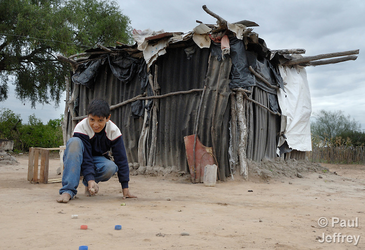 Orlando Garcia, a 9-year old indigenous Wichi boy, plays in the dirt in front of his family's home in Los Dragones, Argentina.
