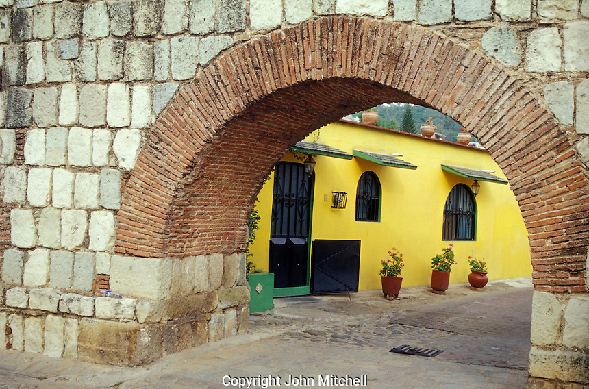 A house framed by one of the arches of Los Arquitos, the remains of an 18th century Spanish aqueduct in the city of Oaxaca, Mexico