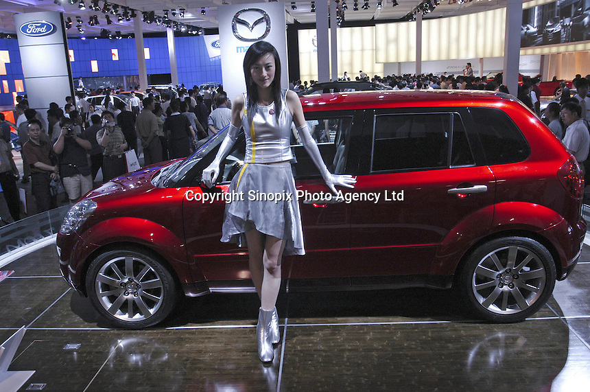 A Chinese model poses besides a Mazda MX Micro Sport at the Auto China 2004 exhibition in Beijing, China..
