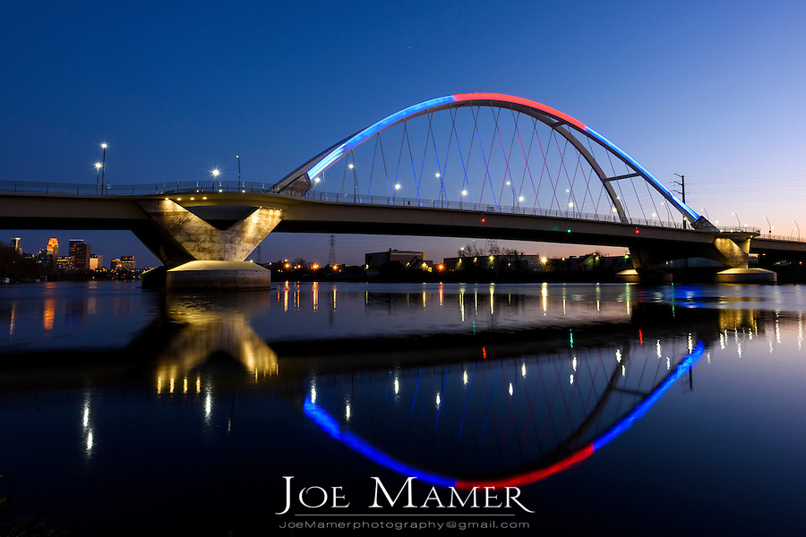 Lowry Avenue bridge at dusk with blue and red lighting.