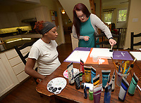 NWA Democrat-Gazette/ANDY SHUPE<br /> Sade Danie (left) and intern Jess Perry prepare to paint canvases Friday, June 29, 2018, as a thank you for donor at Compassion House in Elm Springs. Danie is the first 18-year-old woman to move into Compassion House, a home for pregnant teens, after a policy change made June 11 allowed them to accept 18- and 19-year-olds.