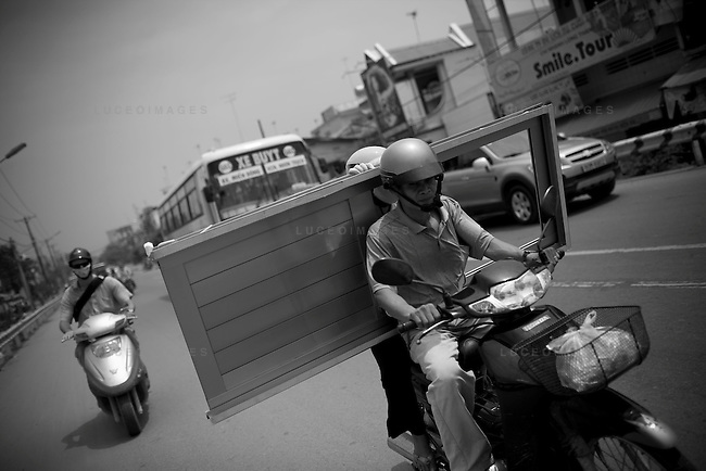 Vietnamese men transport a door on a motor bike in Ho Chi Minh City, Vietnam.