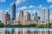 Austin skyline close up across ladybird lake with the reflection of the downtown buildings and puffy white clouds all reflected in the water. You can view all the iconic city buildings like the frost, austonian which make up the modern urban cityscape that is Austin today.