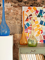 Detail of three coloured glass vases displayed on a plinth and sideboard in front of a large photograph of colourful paint swatches