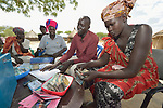 Members of a savings group in Panyagor, a village in South Sudan's Jonglei State, record contributions to their personal accounts during a meeting. The group includes internally displaced persons and those who have returned from refuge outside the war-torn country.<br /> <br /> The group is supported by the Lutheran World Federation, a member of the ACT Alliance.