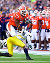 October 31, 2009 - Champaign, Illinois, USA -  Illinois running back Daniel Dufrene (21) leaps over Michigan defensive back Donovan Warren (6) in the game between the University of Illinois and the University of Michigan at Memorial Stadium in Champaign, Illinois.  Illinois defeated Michigan 38 to 13.  ...