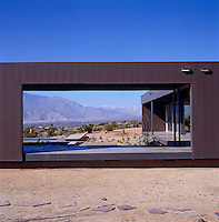 View through part of the steel structure of the modular house with the mountains framed in the distance