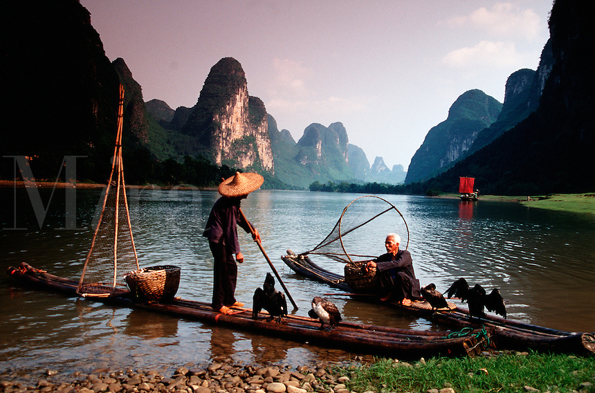 Moody landscape image of Li River Cormorant fishermen on bamboo rafts in the Karst Hills. Guilin Guangxi, China.