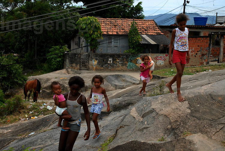 Crianças andam pelo Conjunto de favelas do Alemão. Rio de Janeiro, Brasil.