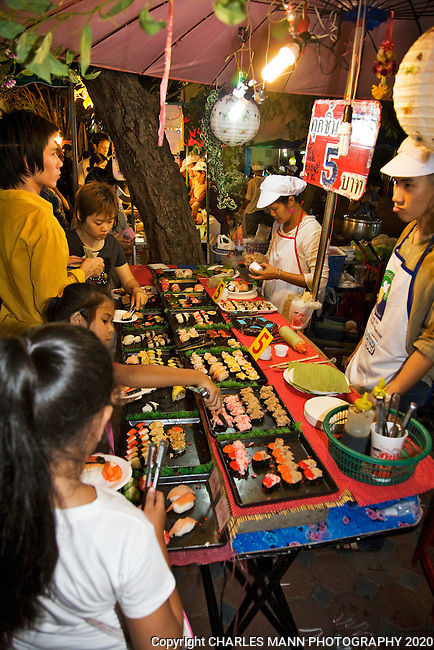 Street food vendors and their customers at the night market in Chiang Mai.