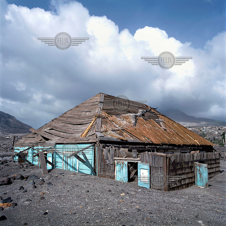 The roof of a destroyed building protrudes from a layer of ash, mud and rock from the pyroclastic flow which descended on the former capital during the Soufriere Hills volcanic eruption. <br /> <br /> <br /> The volcano began erupting in July 1995, and remained active through the subsequent decade. Up to 7,000 of the 10,500 inhabitants have been evacuated from the island, while other residents have been moved to the northernmost areas. The southern region affected by the eruption is designated out of bounds to everyone except scientists.