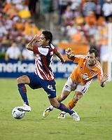 CD Guadalajara forward Sergio Santana (21) dribbles away from Houston Dynamo midfielder Brad Davis (11) during the group stage of the Superliga 2008 tournament at Robertson Stadium in Houston, TX on July 15, 2008.