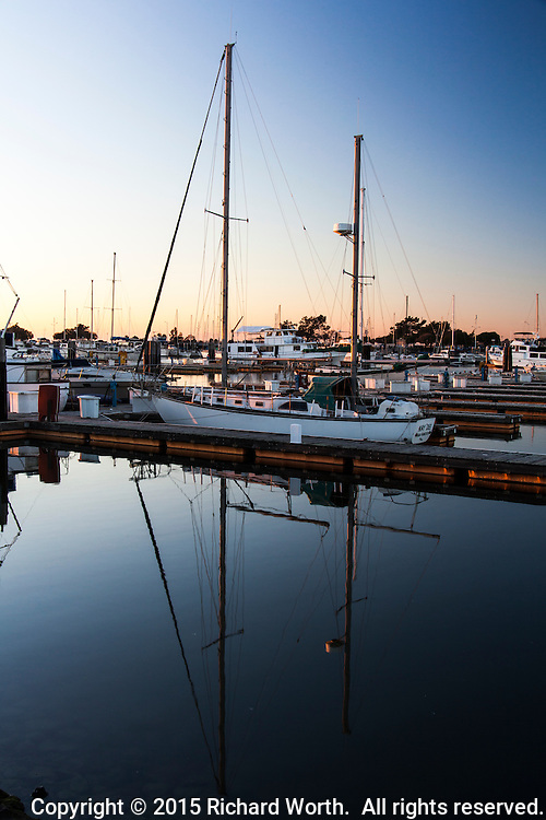 A sailboat at sunset, moored at and reflected in the San Leandro Marina on San Francisco Bay's eastern shore.